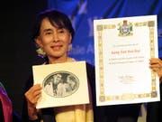 Aung San Suu Kyi mit der Urkunde der Menschenrechtsorganisation Amnesty International, die ihr 2009 den Ehrentitel «Botschafterin des Gewissens» verliehen hatte. Nun hat Amnesty Suu Kyi den Titel entzogen. (Foto: KIM HAUGHTON/EPA) (Bild: KEYSTONE/EPA/KIM HAUGHTON)