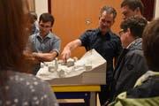 Architekt Florian Schällibaum erklärt den Interessierten das Neubau-Projekt anhand eines Modells. (Bild: Timon Kobelt)