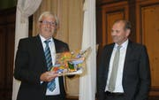 Projektleiter Werner Lenzin übergibt Gemeindepräsident Max Vögeli ein Fotobuch der Sommerkurse. (Bild: PD)