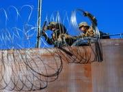 Amerikanische Soldaten verstärken den Grenzzaun zwischen den USA und Mexiko. Am Dienstag versuchten etwas 20 Migranten den Zaun zu erklettern. (Foto: Joebeth Terriquez/EPA) (Bild: KEYSTONE/EPA EFE/JOEBETH TERRIQUEZ)