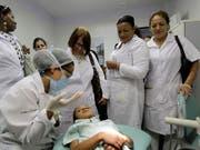 Kubanische Ärztinnen verfolgen eine Zahnbehandlung während einer Trainingsstunde in der Metropole Brasilia. (Bild: KEYSTONE/AP/ERALDO PERES)