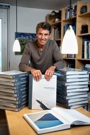 Robert Bösch zu Hause in Oberägeri mit Bücherbergen seines neusten Werkes «Mountains». (Bild: Roger Grütter, 20. November 2018)