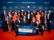 Die Laureus-Family mit dem Check in der Höhe von 1'111'111 Franken (Bild: Keystone/David Biedert)