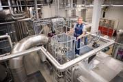 Der Leiter Haustechnik/Umwelt Josef Amrhein auf dem Dampfkessel des Biomasse-Heizkraftwerks. (Bild: PD)