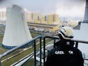 Ein Greenpeace-Mitglied schaut am Dienstag hinüber zum Schornstein des Kohlekraftwerks im südpolnischen Belchatow, den neun Aktivisten erklommen. (Bild: Keystone/AP)
