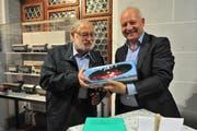Matthias Halter, Präsident des Historischen Museums Uri (rechts), schenkte Remigi Joller an der Vernissage ein Modell eines Rega-Helikopters. (Bild: Urs Hanhart, 27. November 2018)