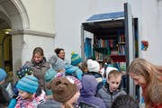 Die Primarschüler räumen die letzten Bücher in die selbstbemalten Regale ein. (Bild: GWF)