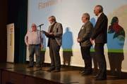 Nach der Bürgerversammlung wurde der Flawiler Preis verliehen. Hans Ruedi Fischer (am Mikrofon) hält eine Laudatio auf den Preisträger Heinz Niedermann (links), Gemeinderat Eddie Frei und Gemeindepräsident Elmar Metzger hören zu. (Bild: Tobias Söldi)