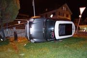Das Auto kam auf der Seite im Garten zu liegen. (Bild: Zuger Polizei)