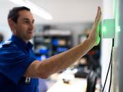 Ein Polizist demonstriert einen zu Testzwecken montierten Handvenen-Scanner. Die Stadtpolizei St. Gallen führt das biometrische Identifikationssystem ein, um die Sicherheit zu verbessern. (Bild: Keystone/GIAN EHRENZELLER)