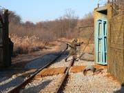 Ein Soldat öffnet ein Grenztor zwischen Nord- und Südkorea, damit ein Zug mit südkoreanischen Experten passieren kann. Die Delegation soll den Zustand des Schienennetzes prüfen, damit später die zwischenstaatlichen Eisenbahnverbindungen wieder aufgenommen werden können. (Bild: KEYSTONE/EPA YNA POOL/YONHAP / POOL)