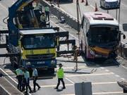 Nach der tödlichen Kollision zwischen einem Bus und einem Taxi in Hongkong räumen Arbeiter das Buswrack von der Autobahn. (Bild: KEYSTONE/EPA/JEROME FAVRE)