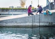 Drei Mädchen fischen Güsel aus dem See.