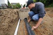 Ein Mitarbeiter der Elektro Niklaus AG bei der Rohrmontage im Erdreich für Kabel-TV. (Bild: PD)