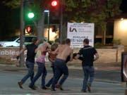 Junge Leute bringen einen Verletzten aus der Borderline-Bar in Thousand Oaks, Kalifornien, nachdem dort ein Mann auf feiernde Gäste geschossen hat. (Bild: KEYSTONE/AP RMG News)