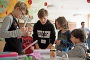 Die Lehrer Nando (links) und Janis (Mitte) bauen mit Kindern eine Papierbrücke. (Bild: Corinne Glanzmann (Luzern, 8. November 2018))