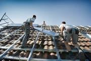 Handwerker montieren Solarpanels auf einem Hausdach. (Bild: Urs Bucher)