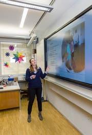 Bettina Wagner testet eine elektronische Wandtafel, die bald in allen Schulzimmern installiert wird. Auf der Rückseite des Whiteboards findet sich eine Schiefertafel – wie in guten alten Zeiten. (Bild: Thomas Hary)
