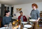 Die Gastgeberinnen Nadia Kaufmann (links) und Alexandra Weibel sowie Biniam Gebreab aus Eritrea beim gemeinsamen Abendessen. (Bild: Stefan Kaiser (Zug, 10. Dezember 2018))