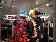 Sonderverkaufs-Plakate und Christbäume gleichzeitig: In der Modebranche ist das mittlerweile üblich, wie dieses Beispiel zeigt. (Bild: hor)