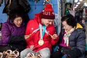 Bewundert: Olympiasieger Theo Gmür im Austausch mit Einheimischen. (Bild: Alexandra Wey/Keystone (Pyeongchang, 16. März 2018))