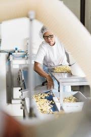 Un employé inspecte l'emballage des bonbons Ricola sur le site de production de Laufen.  (Image: Christian Beutler (20 août 2014))