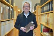 Bürgerarchivar Franz-Xaver Isenring hält das älteste Rechnungs- und Protokollbuch in den Händen. Wegen seines schwarzen Einbandes wird es «Schwarzbüechli» genannt. (Bild: Mario Testa)