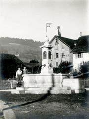 Der Krienser Dorfbrunnen auf dem Dorfplatz, kurz nach der Inbetriebnahme 1918. Hinten das Pfisterhaus, ehemals Bäckerei Fischer. Bild: Privatarchiv
