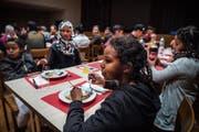 Die Asylsuchenden geniessen das Essen und die gemeinsame Zeit an der Weihnachtsfeier im evangelischen Kirchgemeindehaus. (Bild: Andrea Stalder)