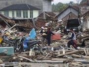 Bewohner suchen in den durch den Tsunami zerstörten Gebäude nach Habseligkeiten. Noch werden viele Menschen vermisst. (Bild: Keystone/EPA/ADI WEDA)