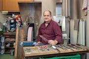 Leo Cozzio in der Werkstatt seiner Messerschmiede in Gossau. Hier schärft er Messer, Scheren und andere Werkzeuge. (Bild: Urs Bucher)