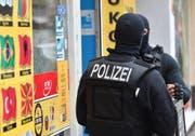 Vermummte Einsatzkräfte stehen vor einem Kiosk im Stadtteil Neukölln. Die Berliner Polizei ging im September gegen kriminelle arabische Grossfamilien vor. Bild: Paul Zinken/Keystone (Berlin, 5. September 2018)