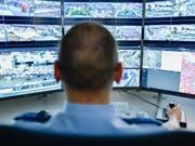 Ein Polizist sitzt im Polizeipräsidium an einem Arbeitsplatz der sogenannten intelligenten Videoüberwachung. Die Stadt Mannheim startet mit einer Videoüberwachung, die verdächtige Bewegungen auf öffentlichen Plätzen frühzeitig erkennen soll und den Sicherheitsbehörden meldet. (Bild: Keystone/DPA/UWE ANSPACH)