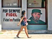 Für immer Fidel - Fidel ist das Volk. Die Kubanerin in Havanna scheint der Spruch an der Hauswand wenig zu beeindrucken. (Bild: KEYSTONE/EPA EFE/YANDER ZAMORA)