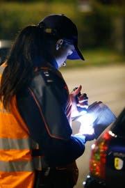 Eine Polizistin kontrolliert einen Fahrzeugausweis. Bild: Stefan Kaiser