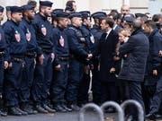 Stark unter den Druck der Strasse geraten: Frankreichs Präsident Emmanuel Macron mit Einsatzkräften gegen gewalttätige Ausschreitungen am Sonntag. (Bild: KEYSTONE/EPA/ETIENNE LAURENT)