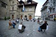 """Die Organisation """"Integrale Politik"""" inszeniert einen politischen Schweigekreis. dabei sitzen die Mitglieder schweigend auf dem Kornmarkt. (Bild: Dominik Wunderli / Neue LZ)"""