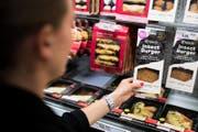 Eine Coop-Verkäuferin im Laden bei Canobbio nimmt eine Packung mit Burgern aus Mehlwürmern aus dem Kühlregal (Archivbild). (Bild: Gabriele Putzu/Keystone/TI-Press (Lugano, 21. August 2017))