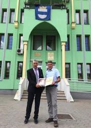 Esad Canic, Präsident des Stadtparlaments von Kalesija (links), überreicht dem ehemaligen Zuger Stadtschreiber Arthur Cantieni vor dem Rathaus von Kalesija die Goldene Plakette. (Bild: PD)