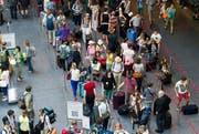 Reisende warten in der Hochsaison am Flughafen Zürich vor der Gepäckaufgabe. (Bild: Keystone)