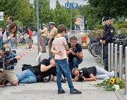 Kampf um das beste Bild: Fotografen machen Bilder von Blumen am Tatort des Münchner Amoklaufs vom 22. Juli. (Bild: AP/Jens Meyer)