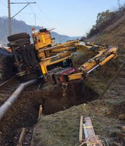Der umgestürzte Bagger auf den Gleisen. (Bild: BLS)