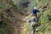 Zwei Arbeiter bringen Steinschlagschutznetze an. (Symbolbild) (Bild: Archiv Neue LZ)
