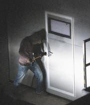 Ein Mann versucht, die Tür eines Kellers aufzubrechen(gestellte Szene). (Bild: PD)