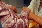 Eine Pflegerin hält einer Hilfsbedürftigen die Hand. (Bild: Archiv Neue LZ)