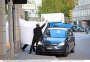 Zürich, 27. Mai: Hotelangestellte schirmen ab, wie ein ranghoher Fifa-Beamter von der Polizei abgeführt wird. (Bild: Pascal Mora/The New York Times)