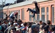 Flüchtlinge klettern bei Gevgelija in Mazedonien in einen Zug nach Serbien, wo sie anschliessend in EU-Länder gelangen wollen. In Brüssel streitet man sich derweil über einen Verteilschlüssel für die Asylsuchenden. (Bild: EPA/Georgi Licovski)