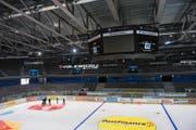 Beim Aufbringen der Werbefolien auf der Eisfläche der Bossard-Arena ist Teamarbeit gefragt. (Bild Maria Schmid)