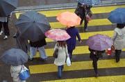 Der Schirm ist Trumpf. Es soll wieder kälter und regnerischer werden Anfang Woche. Im Symbolbild: Die Zürcher Bahnhofstrasse. (Bild: KEYSTONE/Walter Bieri)