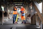 Ivo Burkhalter und Matthias Flühler von der Trigonet AG beim Vermessen der Spreuerbrücke mit Lasertechnologie. (Bild Pius Amrein/Neue LZ)